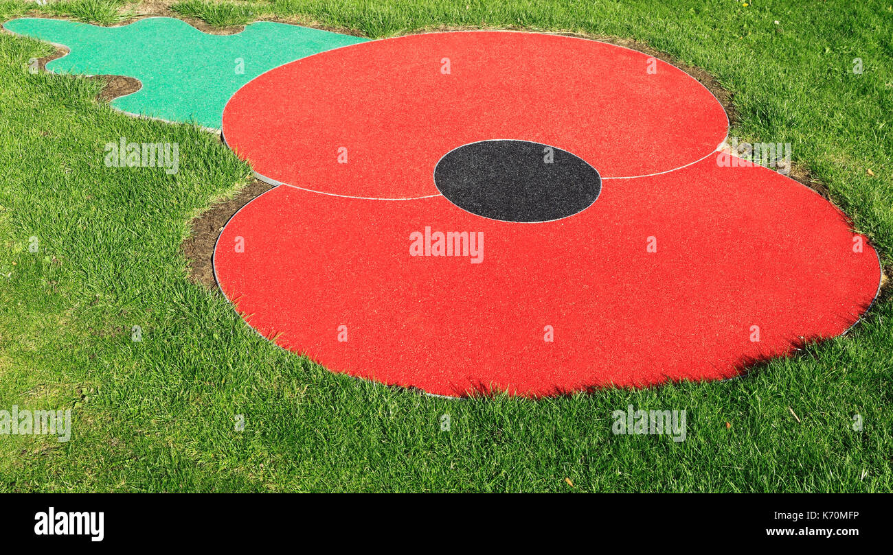 Remembrance Day Poppy, logo, emblem, symbol, set in turf, lawn, grass, Hunstanton, Norfolk, England, UK, war memorial, Stock Photo