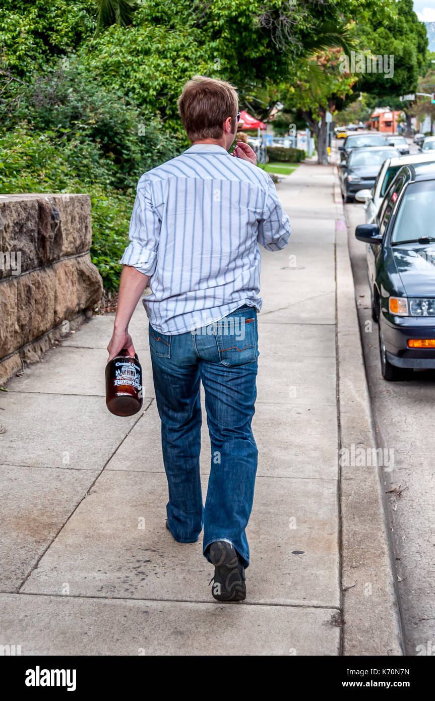 A man walks home carrying a beer growler filled from local brew pub in San Luis Obispo, California, the center of micro brewing on the Central Coast - Stock Image