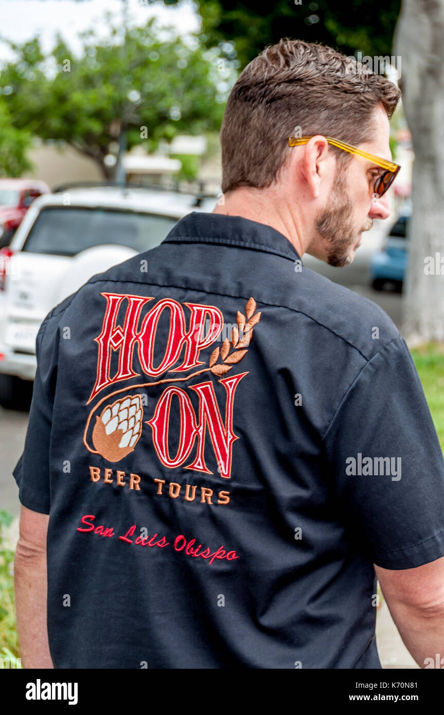 A beer tour guide leads the 'Hop On' brewery tour for tourists visiting San Luis Obispo, on California's Central Coast. - Stock Image