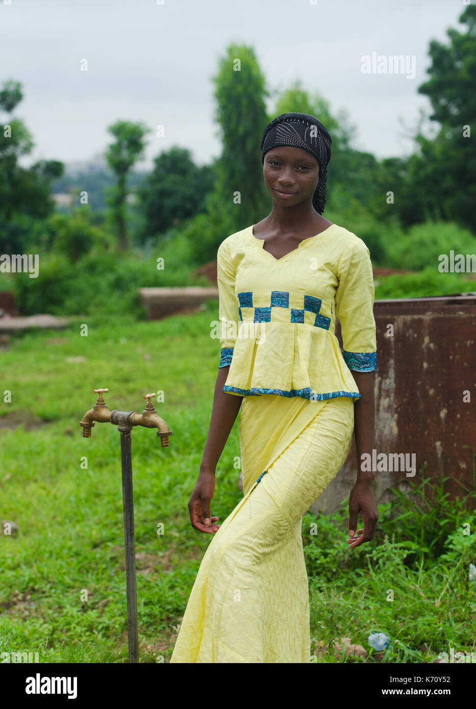 Full body shot of African black girl standing next to water tap in Africa - Stock Image