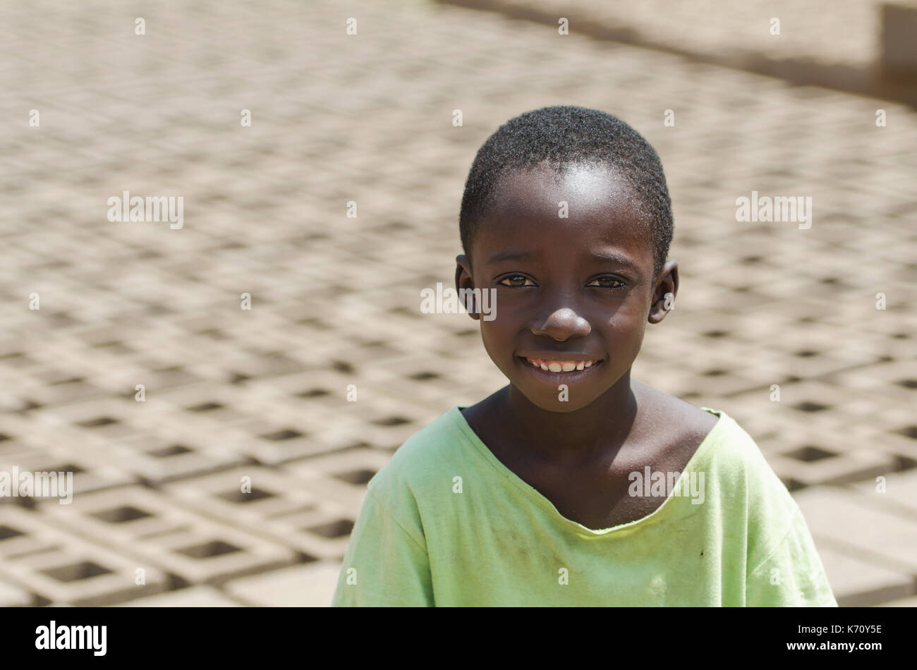 Little African child smiling outdoors behind bricks - Child Labour concept - Stock Image