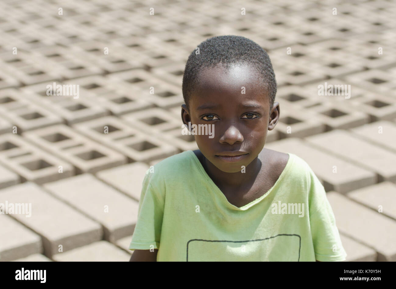Child Exploitation symbol - African black boy with lots of bricks behind him - African Children Labour Labor - Stock Image