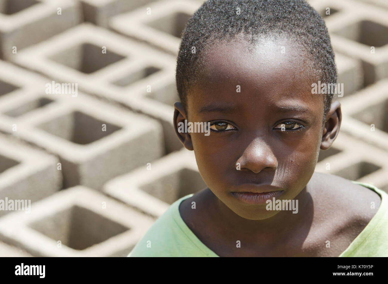Close-up Portrait of African black Boy outdoors as a Child Labour Concept - Working Children - Stock Image