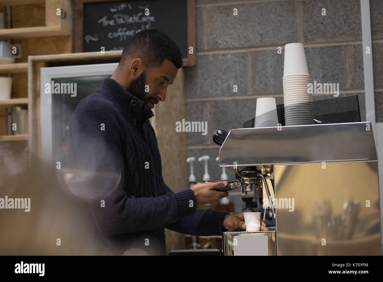 Side view of male owner making coffee in cafe - Stock Image