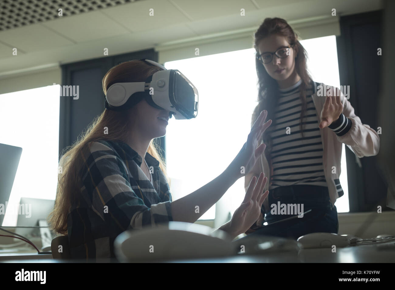 Friends experiencing virtual reality headset in college - Stock Image