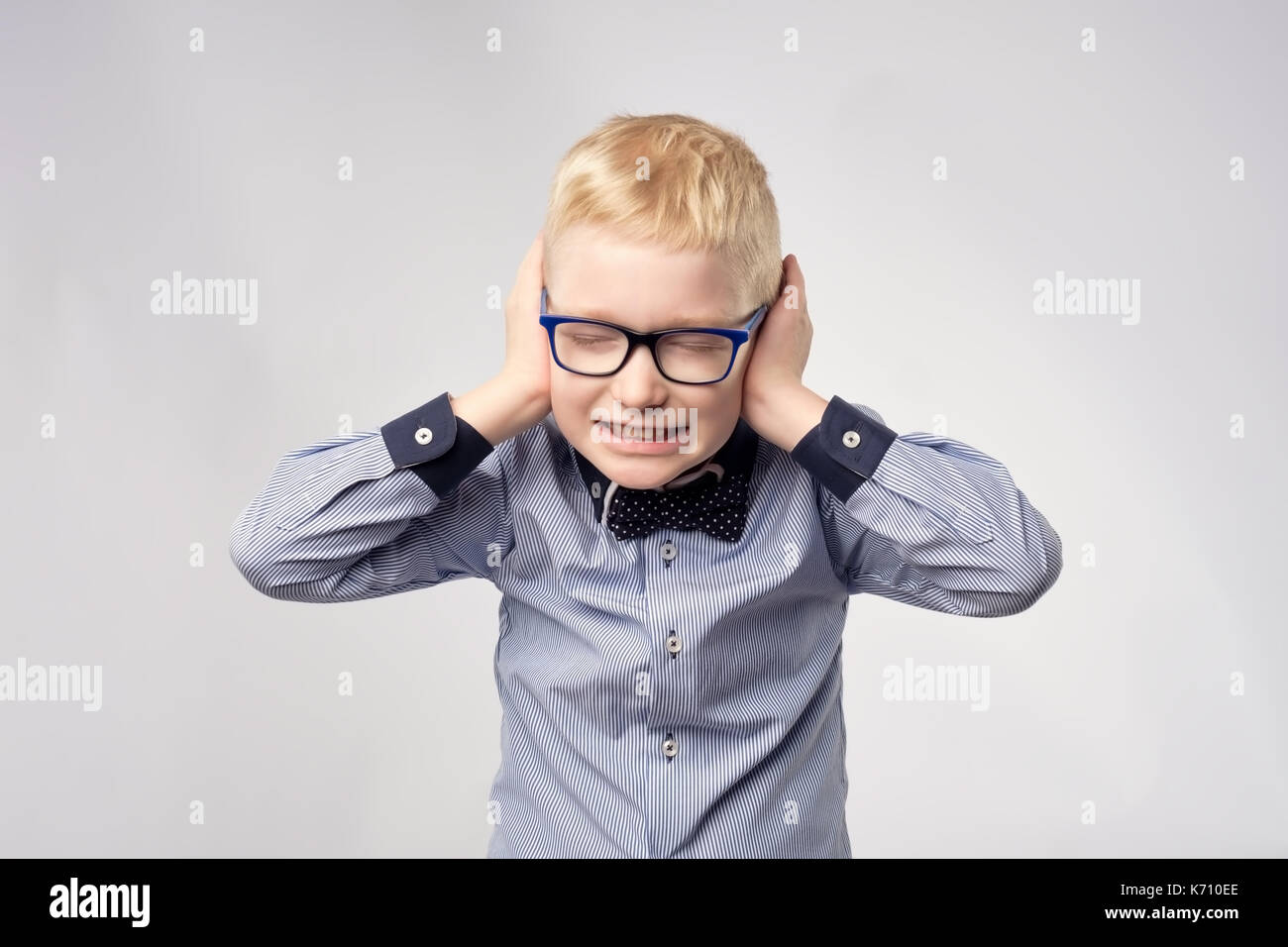 Isolated portrait of gaucasian boy covering ears with hands. Stock Photo