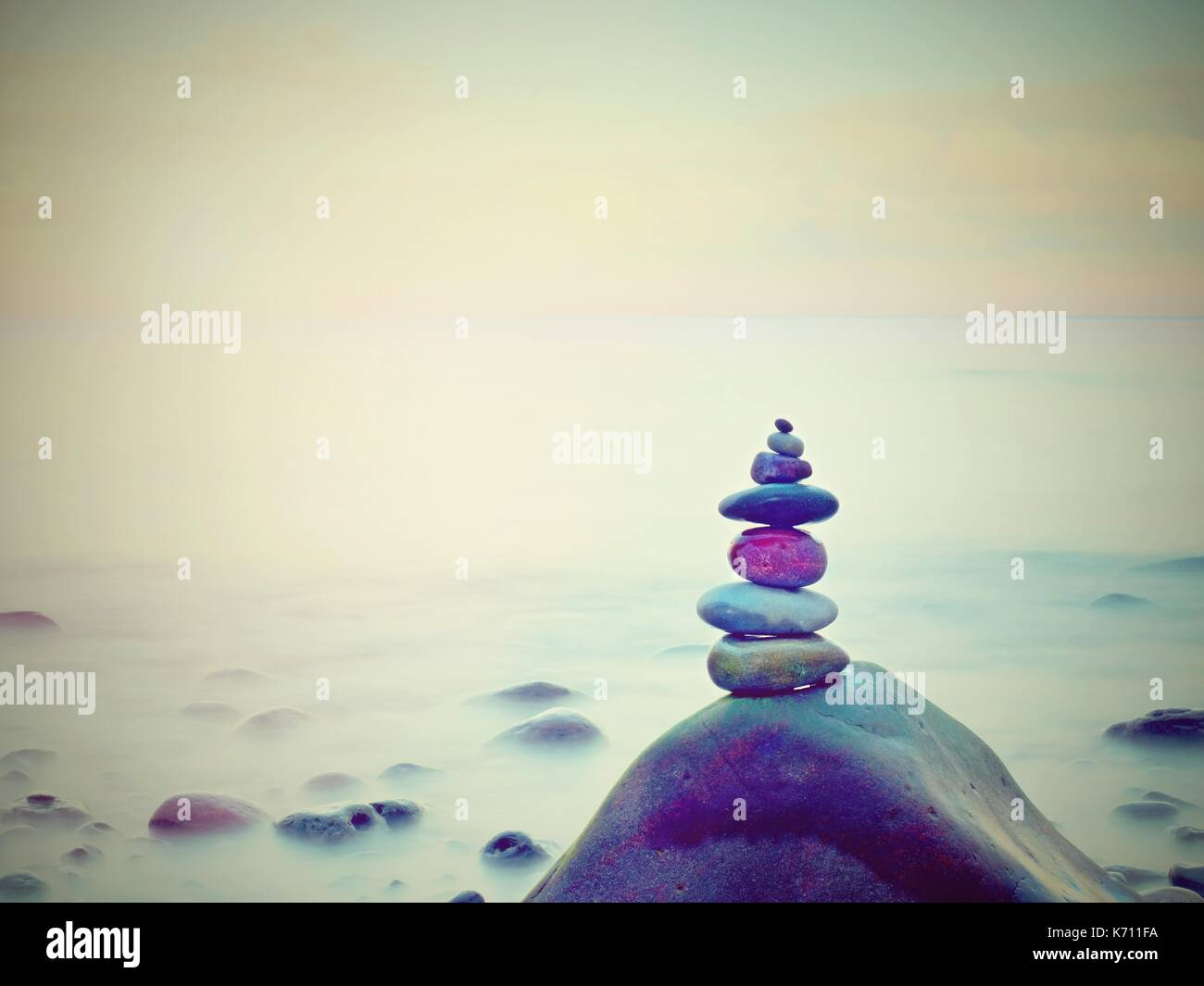 Stones pyramid on pebble beach symbolizing stability, zen, harmony, balance. Tropical sea beach. - Stock Image