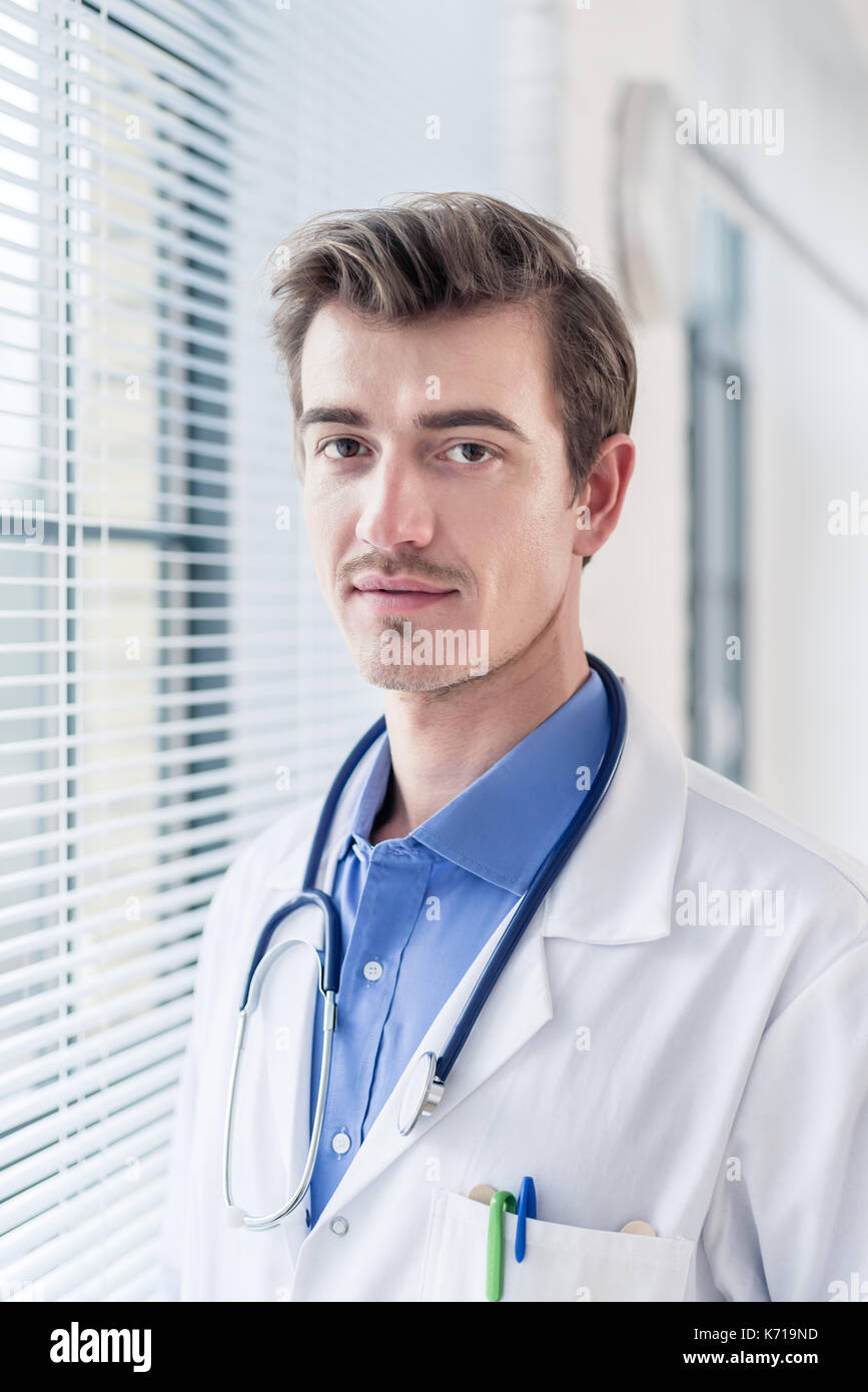 Portrait of a young serious doctor looking at camera with determ Stock Photo