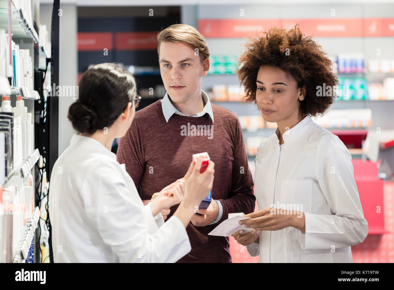 Young man asking for opinion from pharmacists regarding prescrib - Stock Image