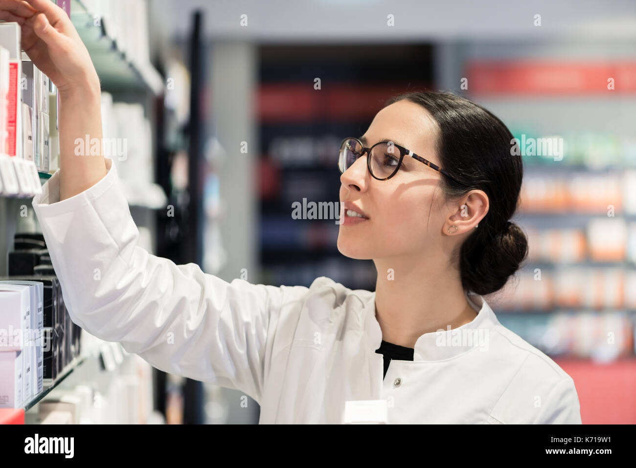 pharmacist standing in front of various products thinking to mak - Stock Image