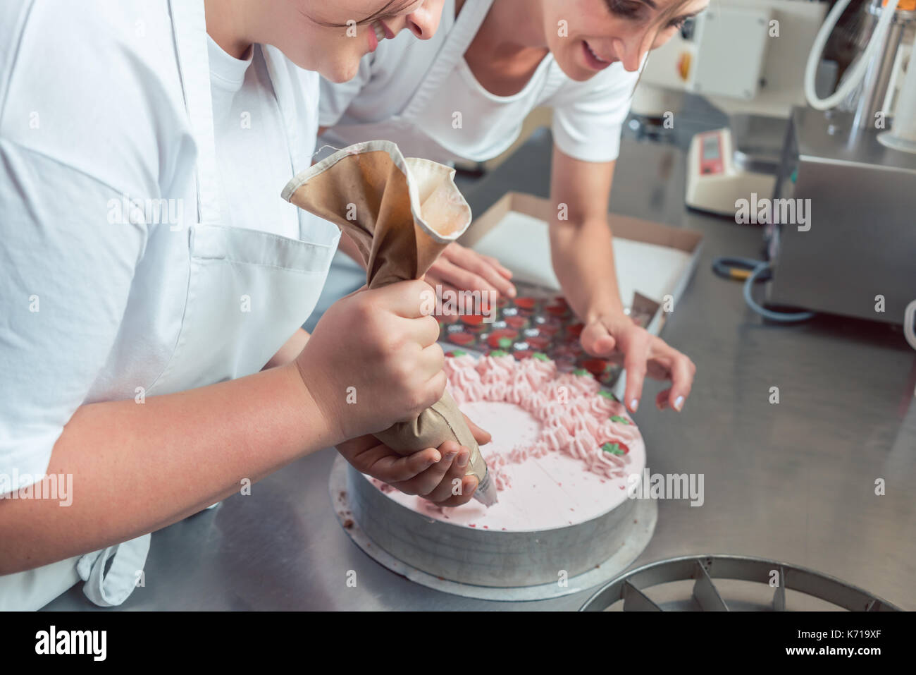 Confectioner women putting cream on cake - Stock Image