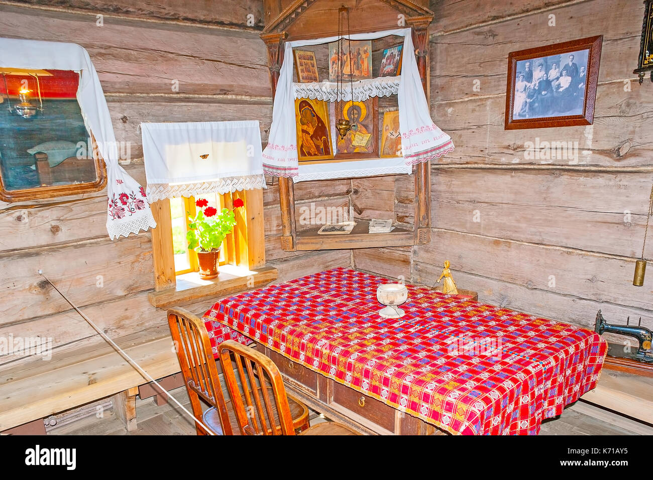 SUZDAL, RUSSIA - JULY 1, 2013: The chamber in old timbered izba of Museum of Wooden Architecture and Peasant Life - the icon in corner over the table, - Stock Image
