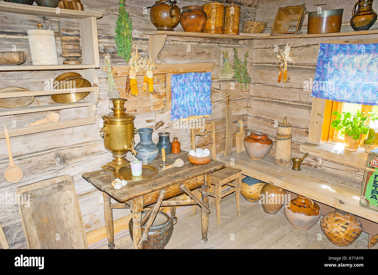 SUZDAL, RUSSIA - JULY 1, 2013: The kitchen in wooden izba in Museum of Wooden Architecture and Peasant Life, the samovar and old preserved tableware a - Stock Image