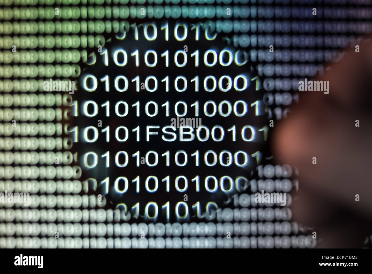 Binary code, Magnifying glass shows russian FSB, intelligence - Stock Image