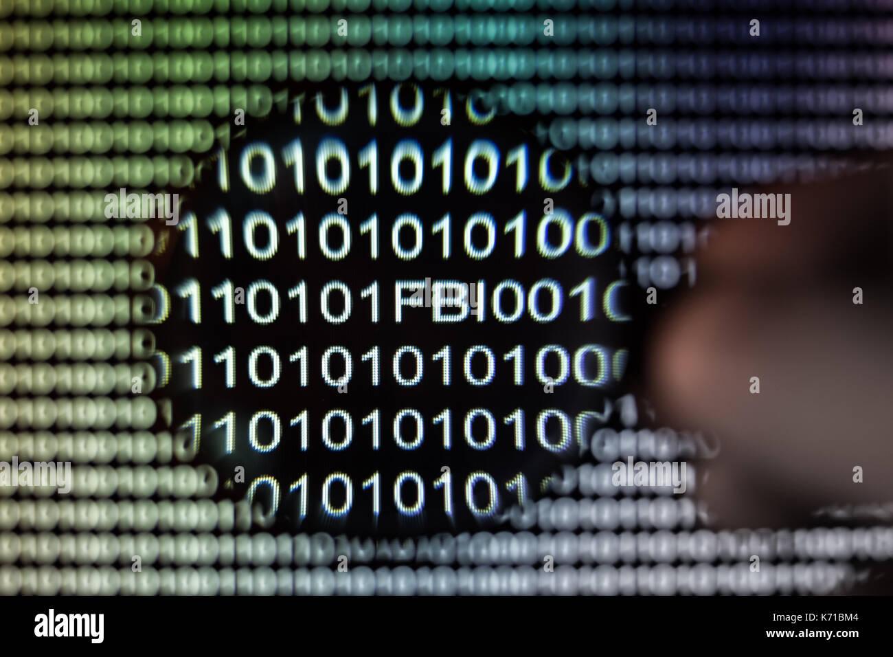 Binary code, magnifying glass shows American FBI, exploit - Stock Image