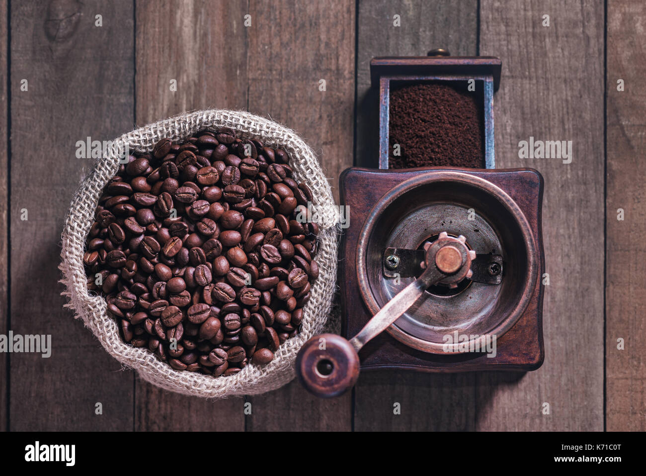 Grinding coffee from roasted beans into a rustic bag. - Stock Image