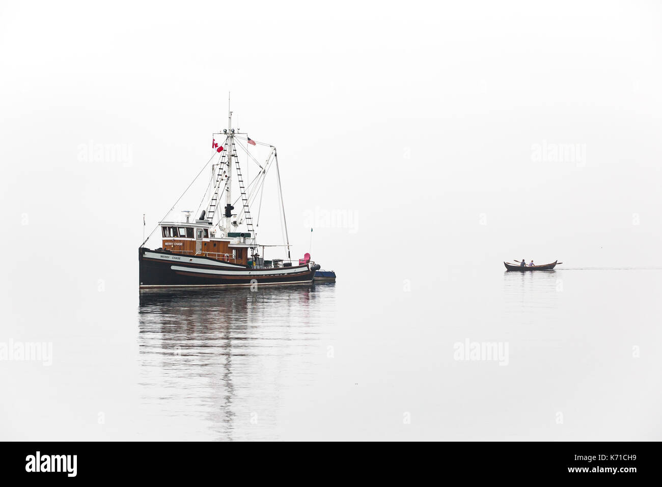 Fishing boat near Port Townsend during Wooden Boat Show in fog with row boat. - Stock Image