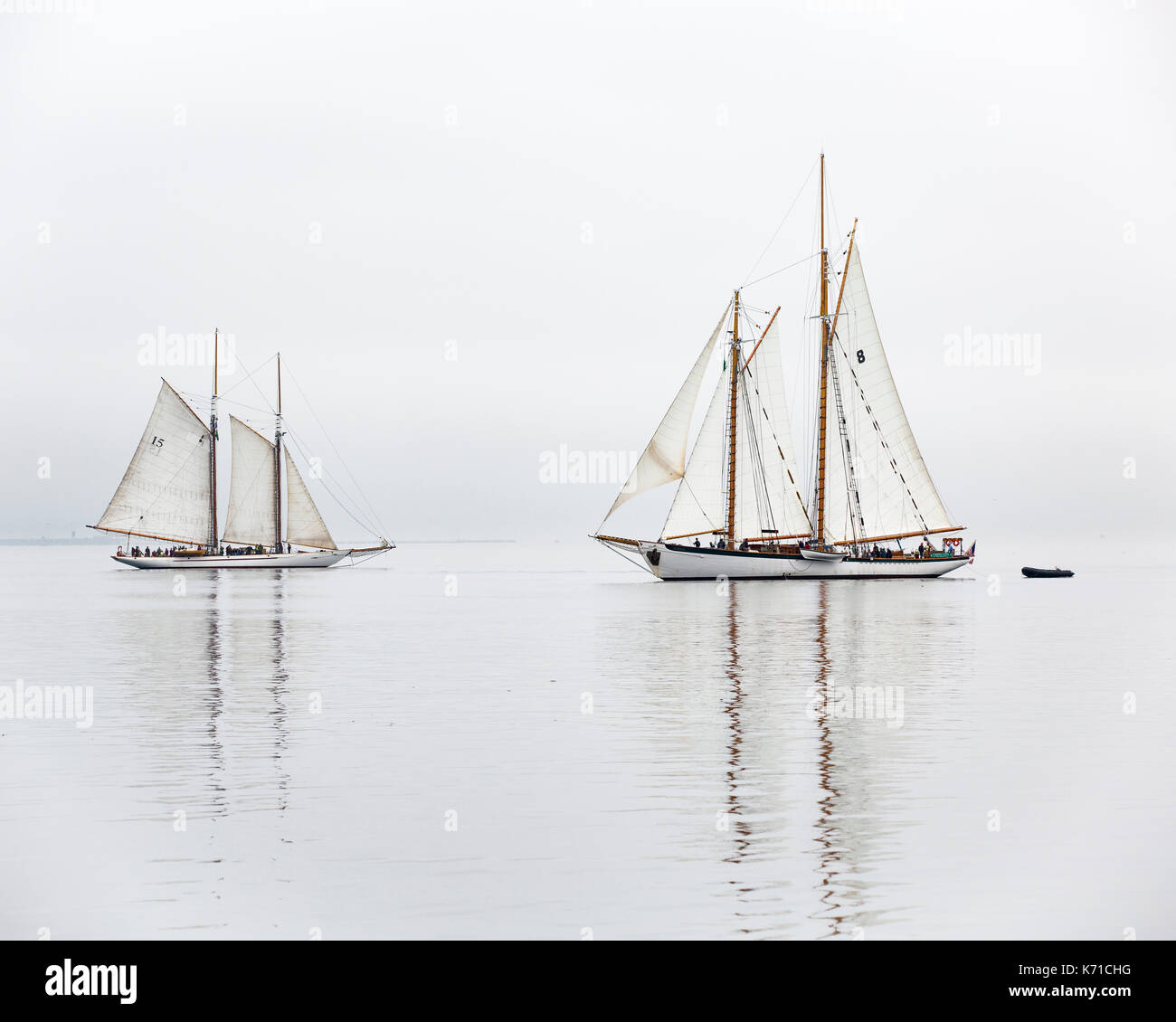 Sailing boat, sailboat wooden schooner yacht Port Townsend, Puget Sound, Washington. Sailing boat Adventuress and Zodiac in fog. - Stock Image