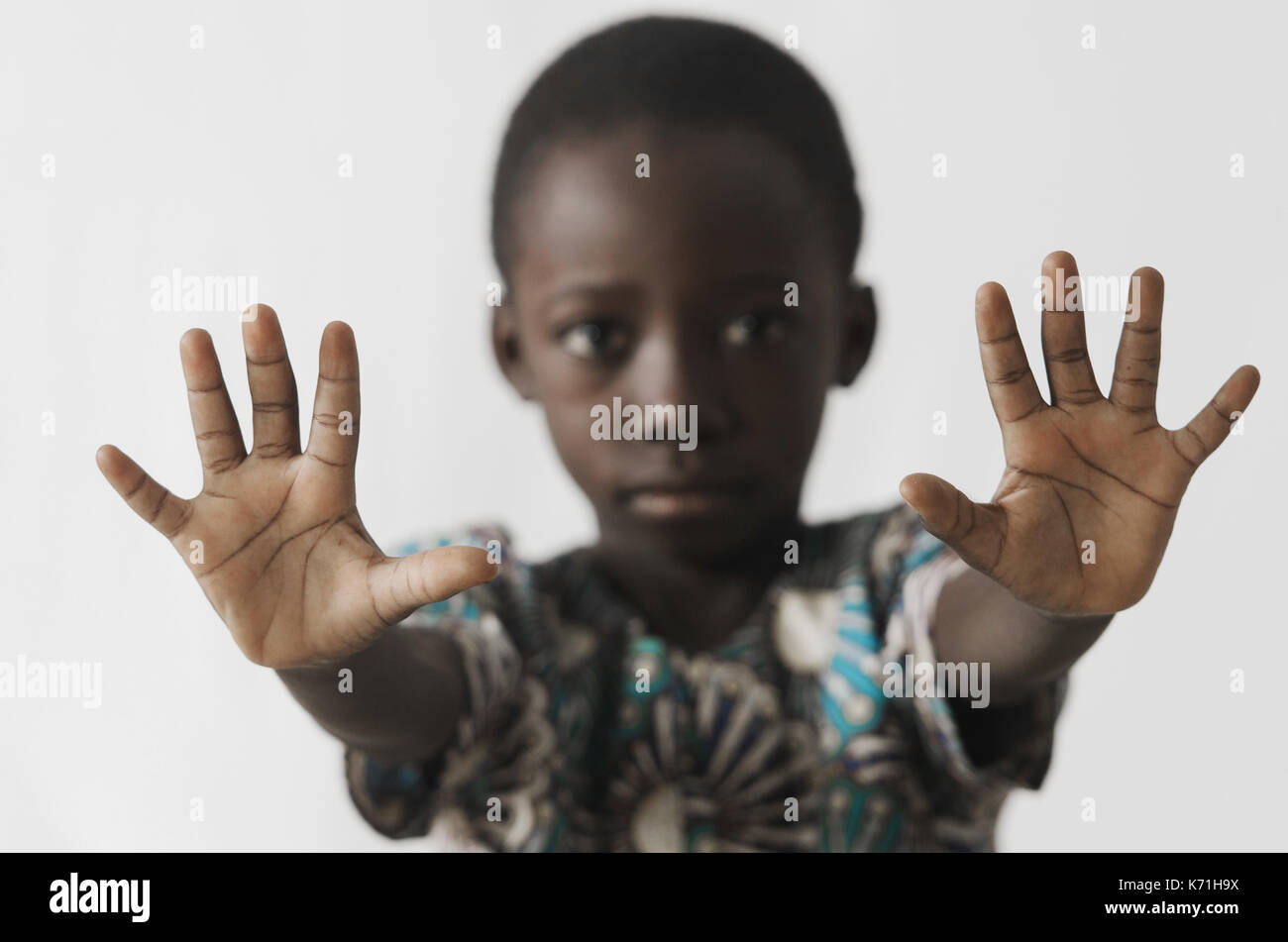 African boy STOP sign with his hands, isolated on white - Stock Image