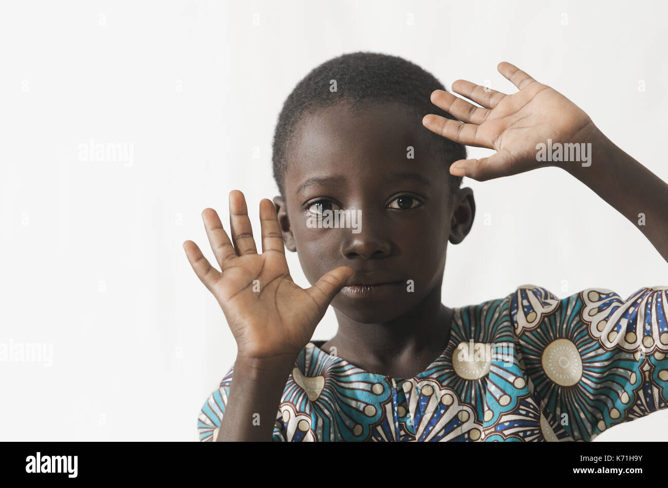 African child protecting his face with his hands, isolated on white - Stock Image