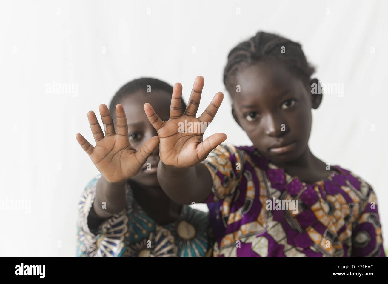 Two African children making stop sign with their hands, isolated on white - Stock Image
