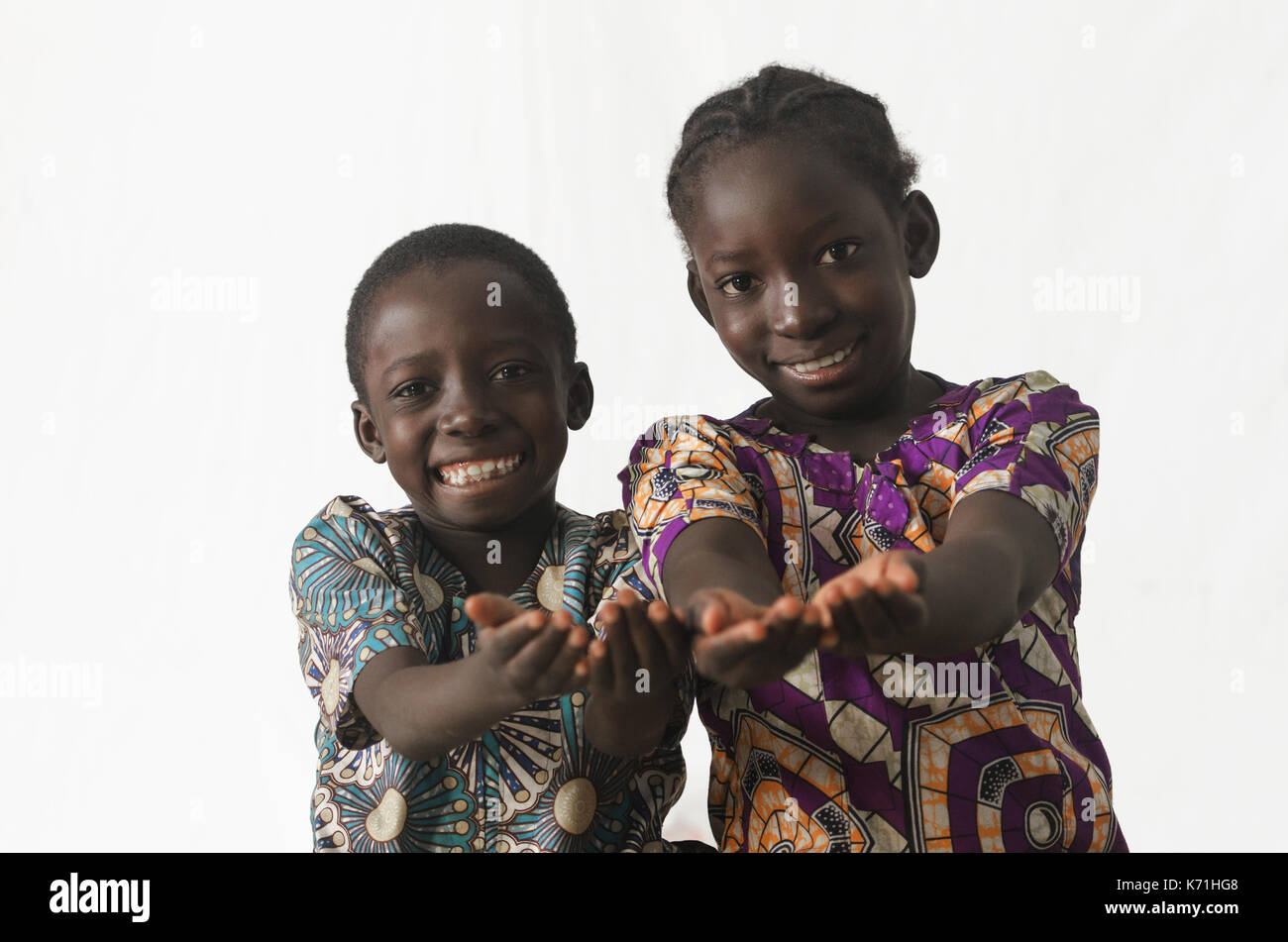 Two African children showing their palms asking begging for something, whilst smiling, isolated on white - Stock Image