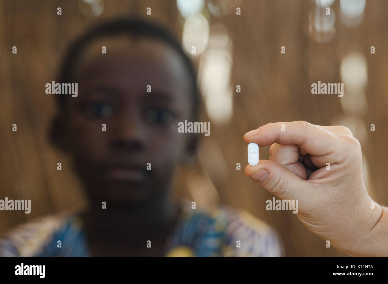 Young African boy getting a medicine pill by a white doctor - Stock Image