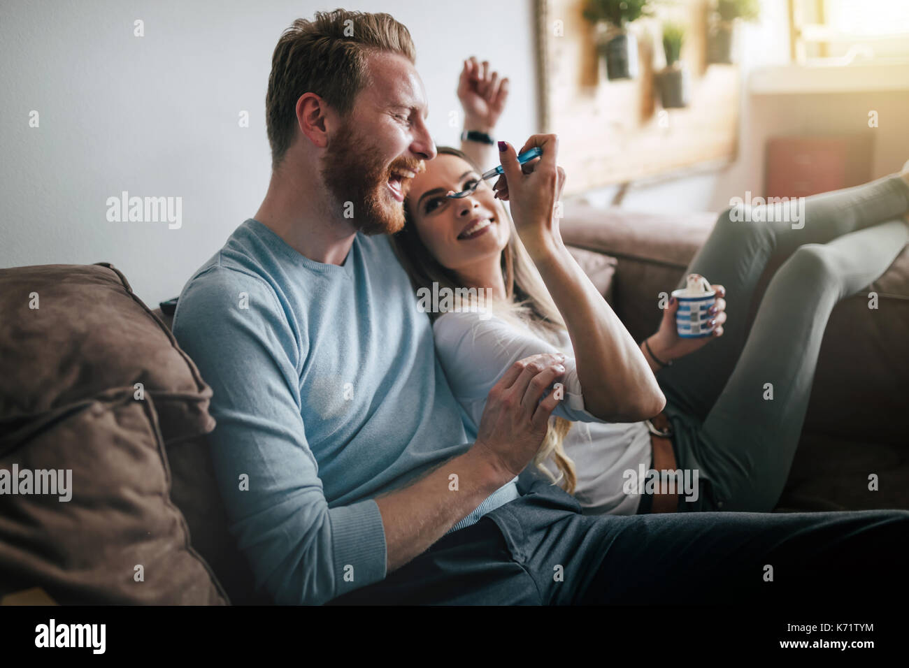 Romantic couple eating ice cream together and watching tv - Stock Image
