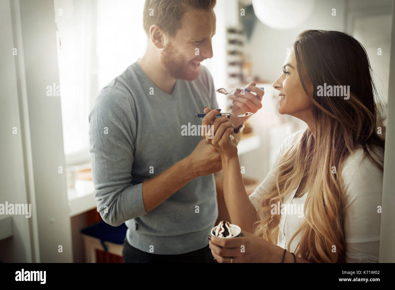 Couple having fun and laughing at home while eating ice cream - Stock Image