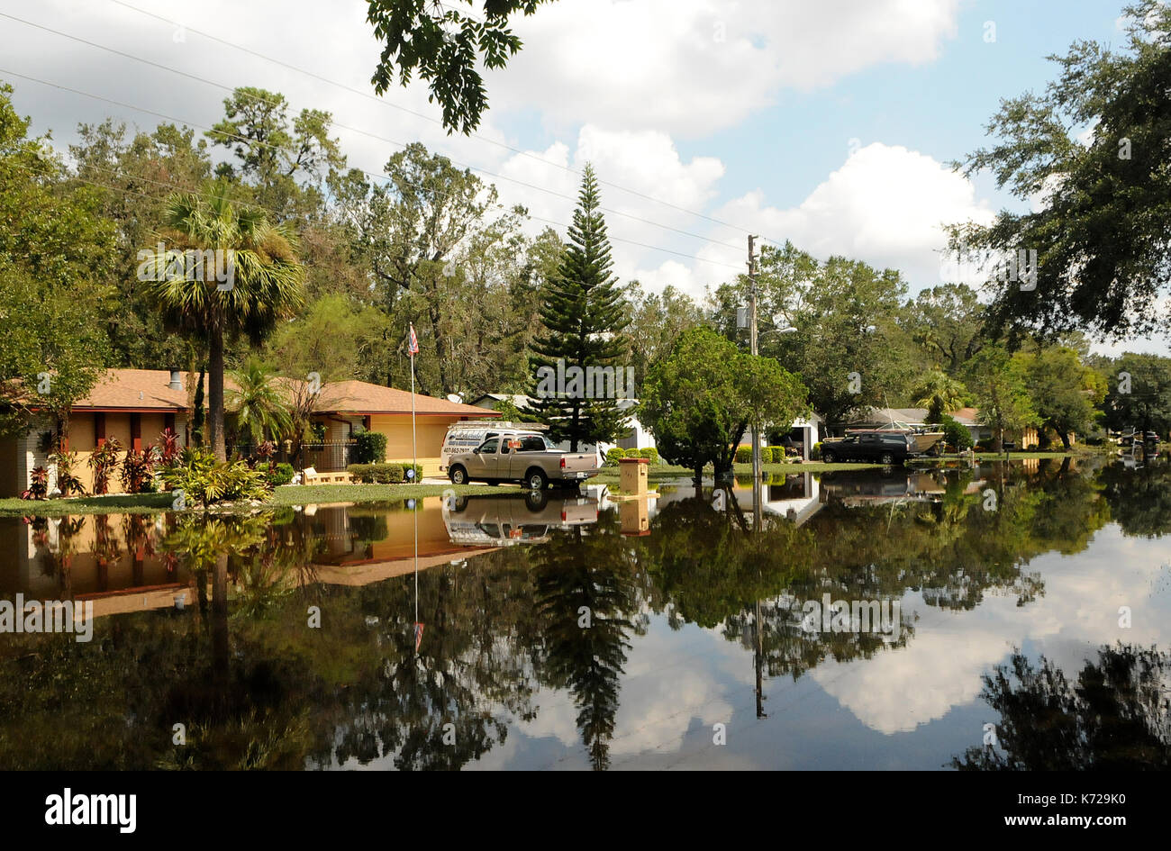 Altamonte Springs, United States. 14th Sep, 2017. September 14, 2017- Altamonte Springs, Florida, United States - Homes and trees are seen reflected in flood waters in the street in the Spring Oaks neighborhood of Altamonte Springs, Florida on September 14, 2017. Emergency workers used boats and trucks to rescue more than 50 residents on September 11, 2017 when water from the nearby Little Wekiva River swamped their homes in the wake of Hurricane Irma. Credit: Paul Hennessy/Alamy Live News - Stock Image