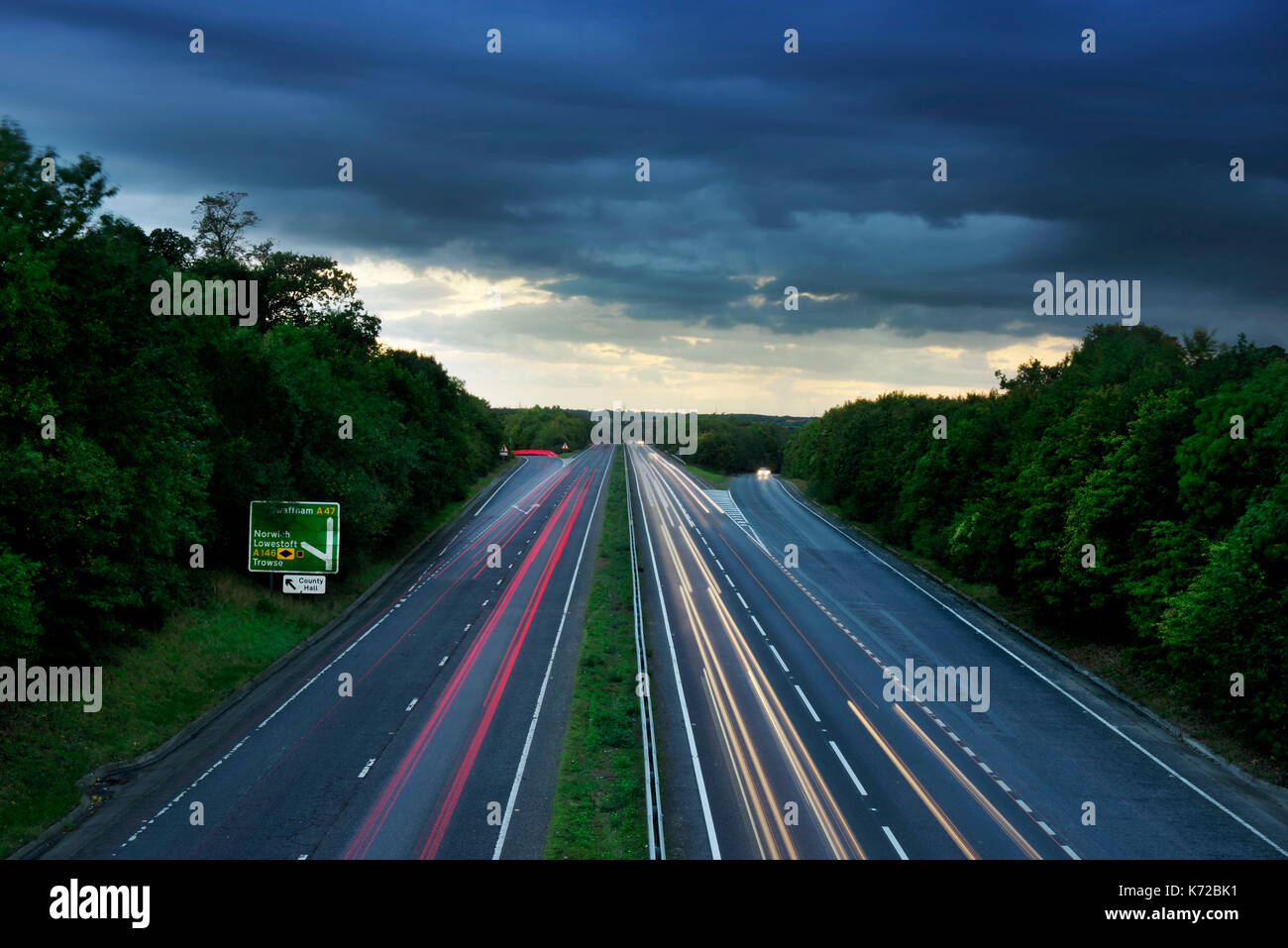 Late evening traffic on the A47 dual carriageway between Norwich and Great Yarmouth, showing the light trails from fast moving cars - Stock Image