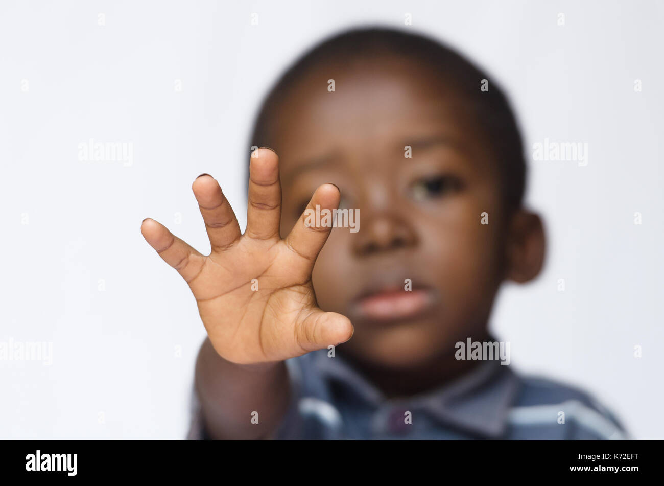 African boy holding his hand out as a STOP sign for racism and abuse - Stock Image