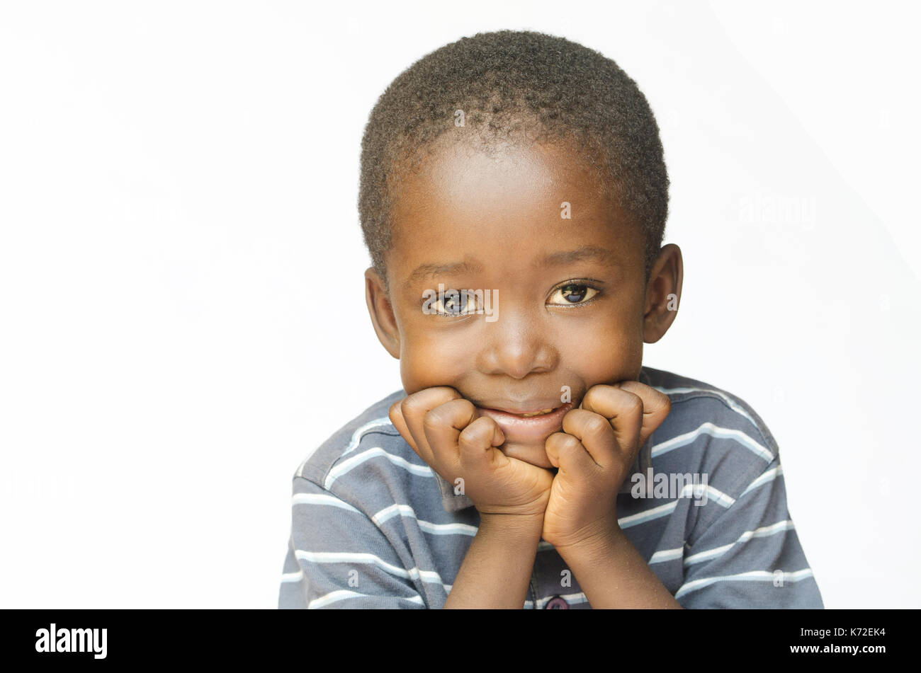 Little African child holding his head in his hands thinking about his future - Stock Image