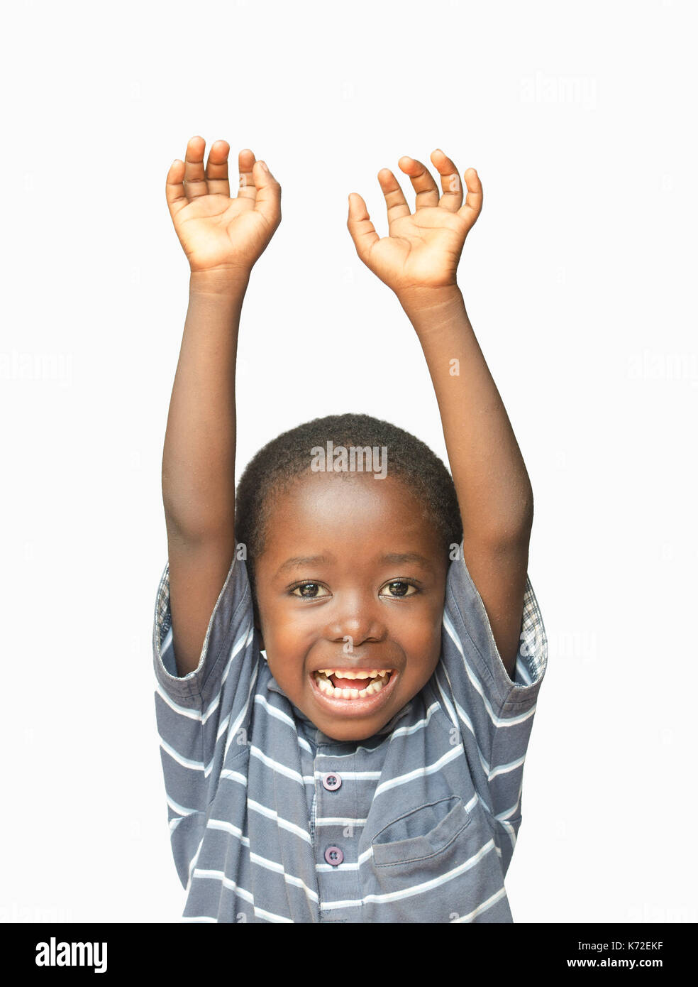 Little African boy holding his hands up in the air whilst laughing and smiling - Stock Image
