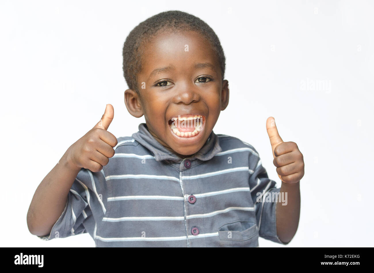 Very happy African black boy making thumbs up sign with hands laughing happily (African ethnicity black boy isolated on white) - Stock Image