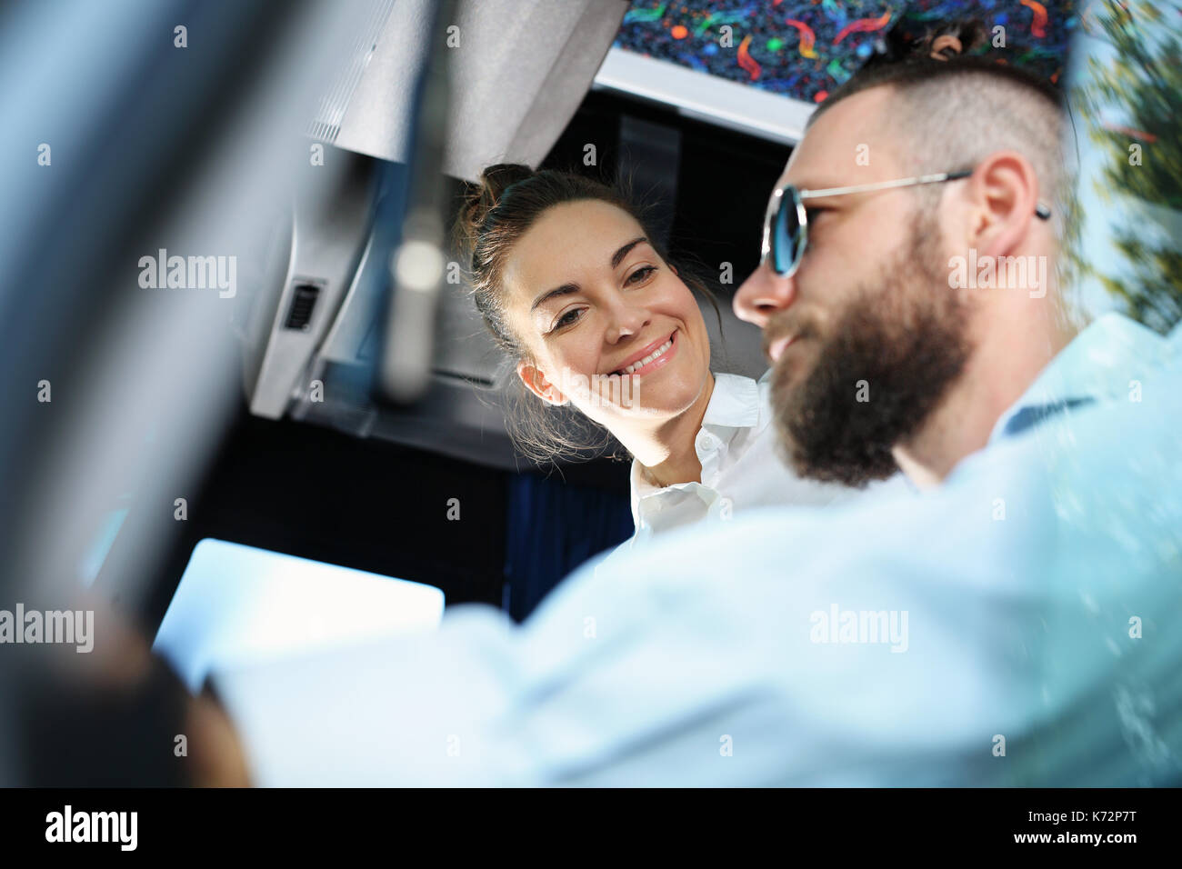 The bus driver drives the vehicle. Bus driver and passenger A bus passenger talking to the bus driver while stationary. - Stock Image