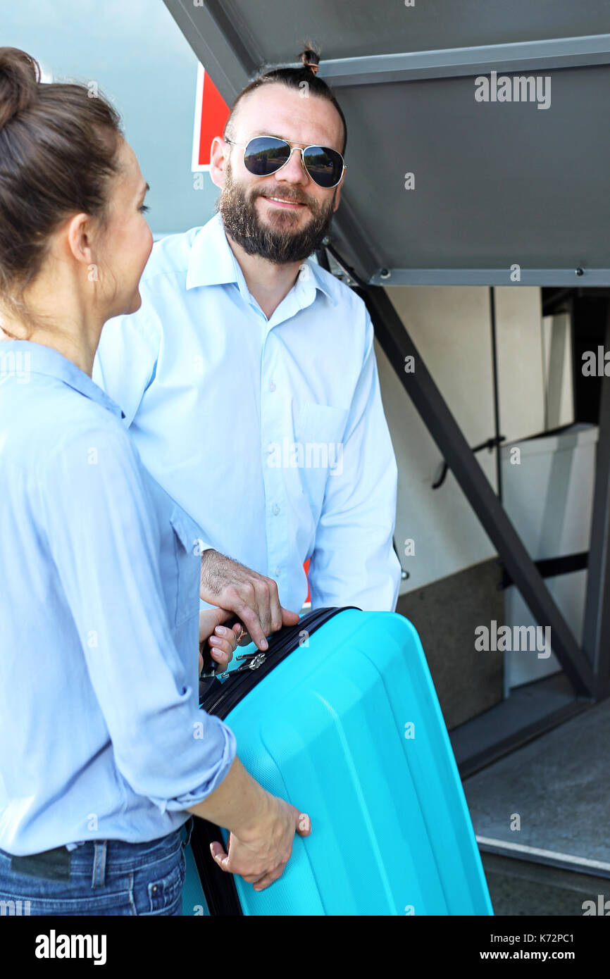 The bus driver gives the baggage to the passenger. - Stock Image