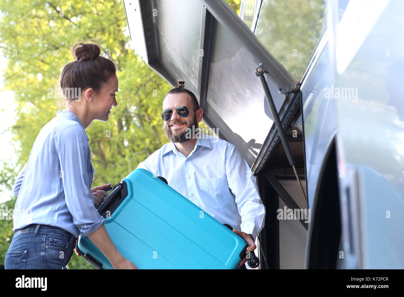 The passenger inserts the suitcase into the luggage compartment on the bus. - Stock Image