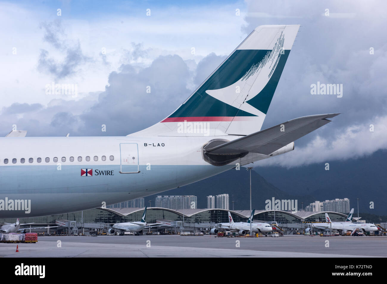 Cathay Pacific brushing logo on the tail of a plane on the tarmac,Hong Kong International Airport Check Lap Kok. Jayne Russell/Alamy Stock Photo - Stock Image