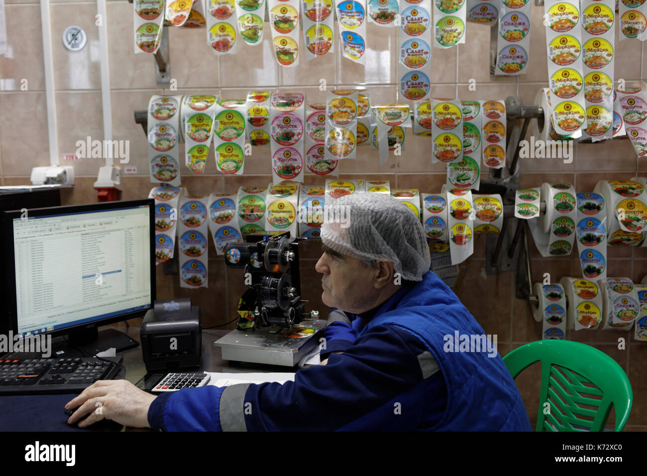 St. Petersburg, Russia - February 28, 2017: Worker in the labelling workshop of the food processing plant. The Factory of Homemade Pickles participate - Stock Image