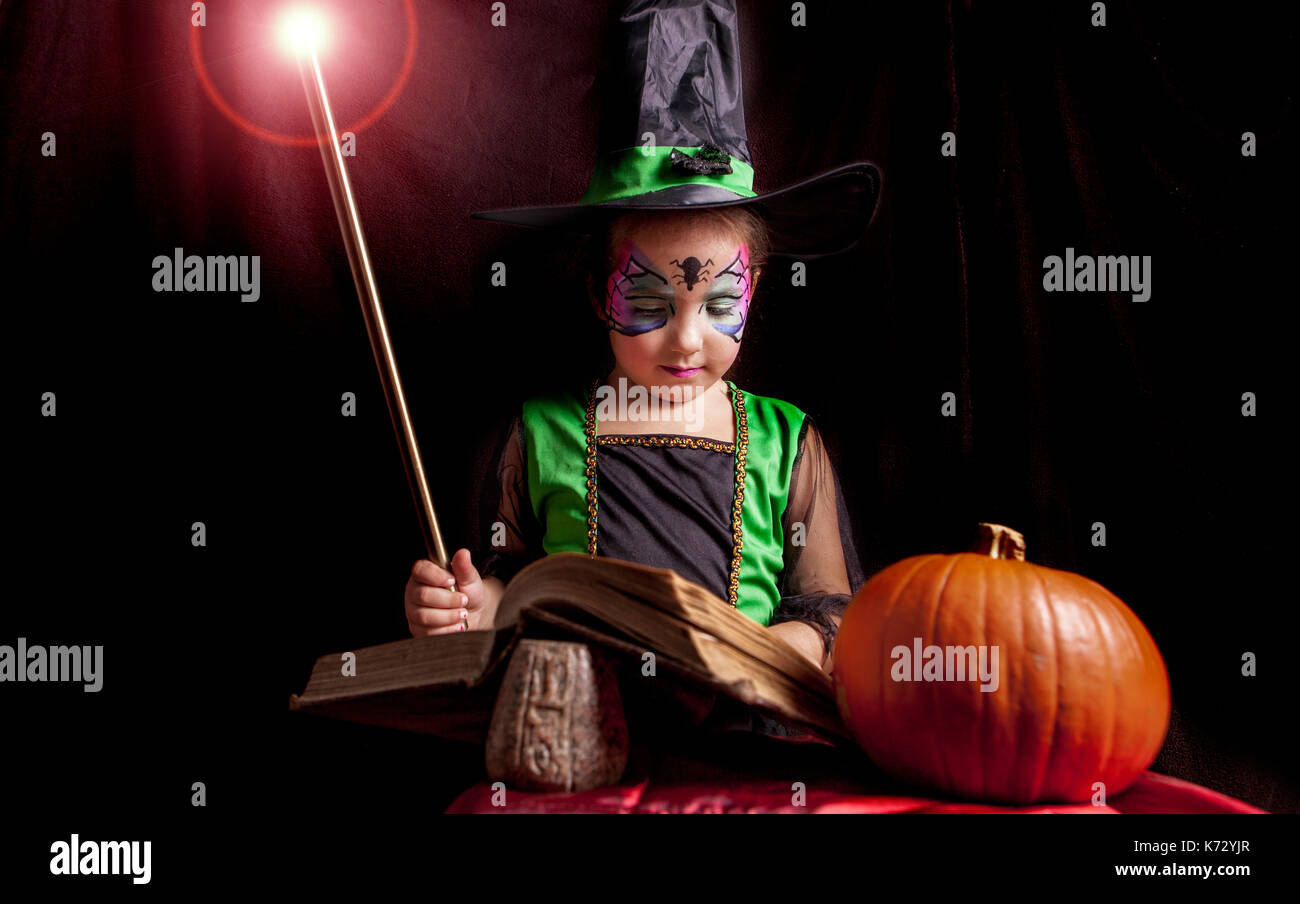 Little cute girl costumed as a witch reads the Book of Spells. Studio take - Stock Image