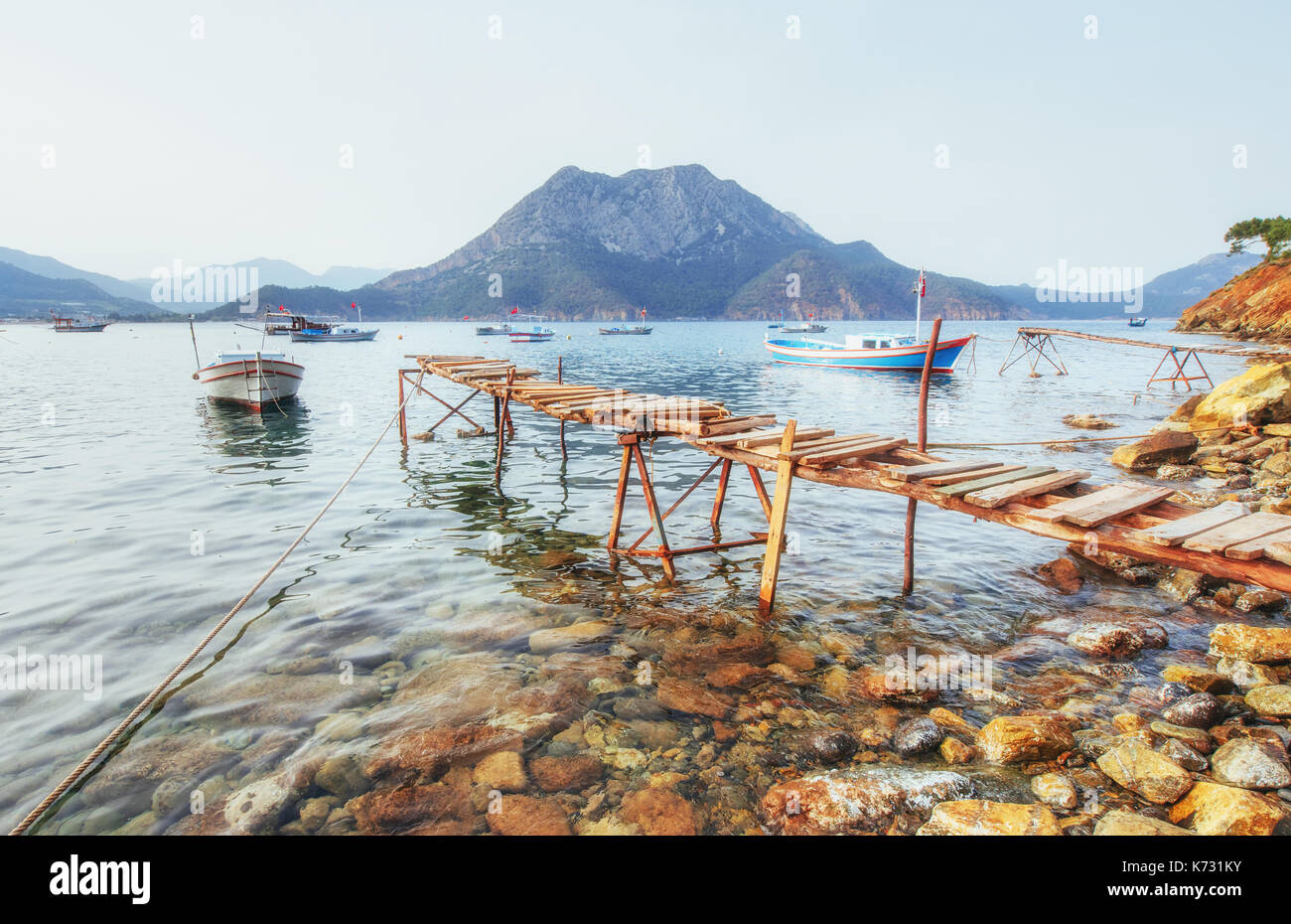 Boats near the broken pier, putting in a tranquil calm blue sea water - Stock Image