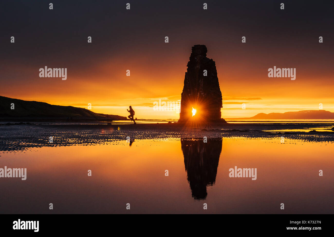 Is a spectacular rock in the sea on the Northern coast of Iceland. On this photo Hvitserkur reflects in the sea water after the midnight sunset - Stock Image