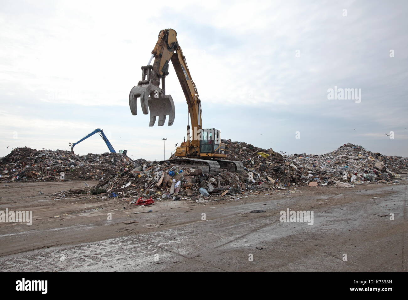 Earth movers organize debris in a makeshift dump in the aftermath of Hurricane Sandy in the Rockaways, New York, New York on November 11, 2012. - Stock Image