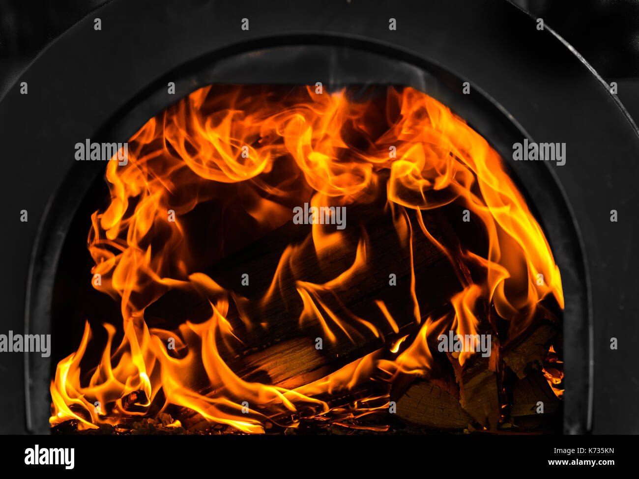 Flames leap from a blazing log in a metal cased wood burning oven - Stock Image