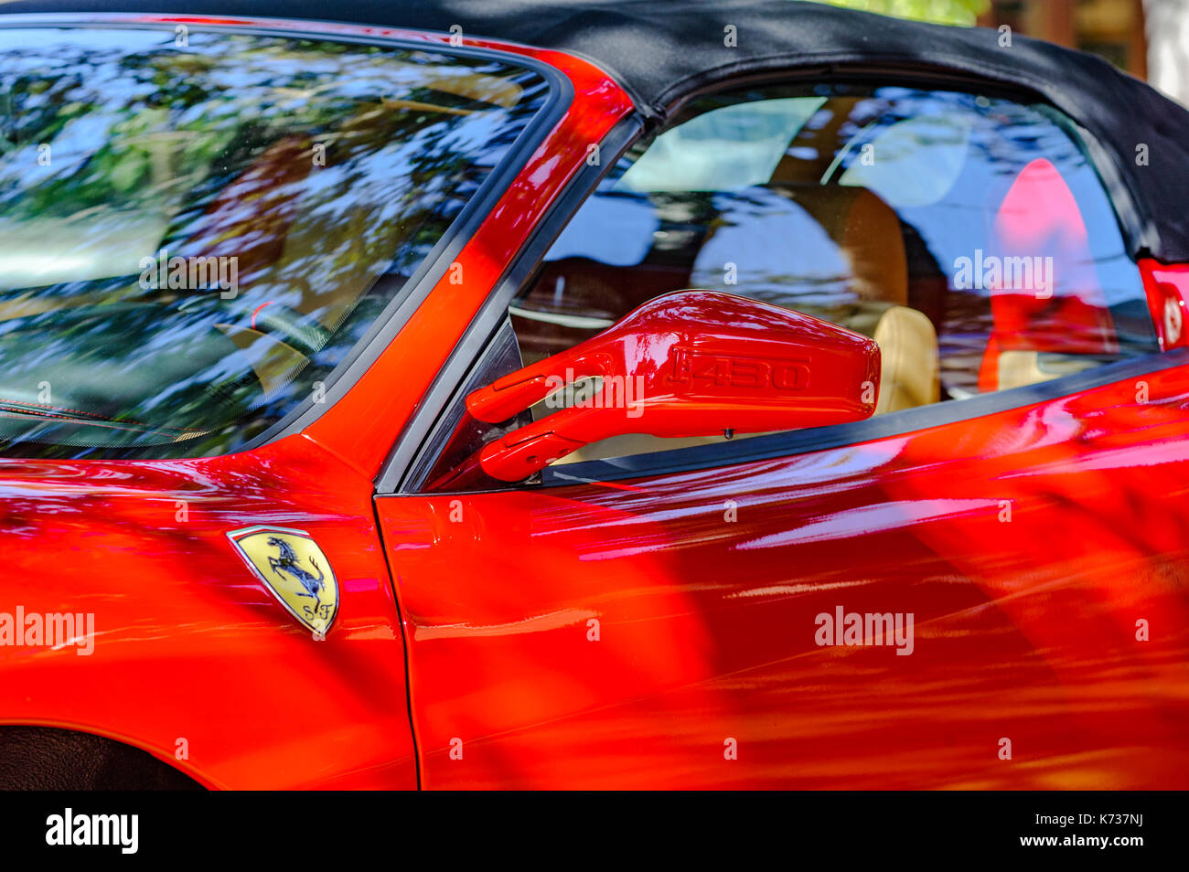 Red Ferrari F430 Spider sports car parked on the street in Hyde Park, Tampa, Florida, United States. The Ferrari is considered a super car. - Stock Image