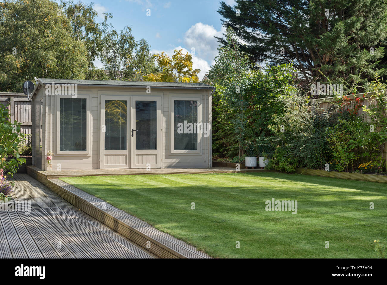 A modern summerhouse / shed in a very well manicured domestic garden - Stock Image