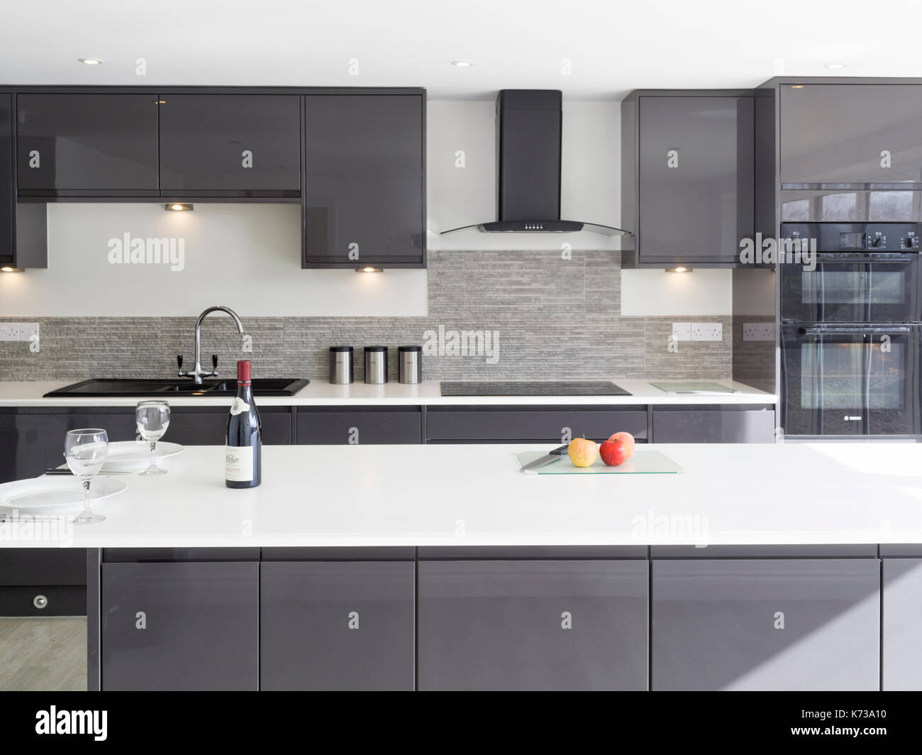 A contemporary, minimal, monochrome domestic kitchen with island and solid countertops in a modern UK home - Stock Image