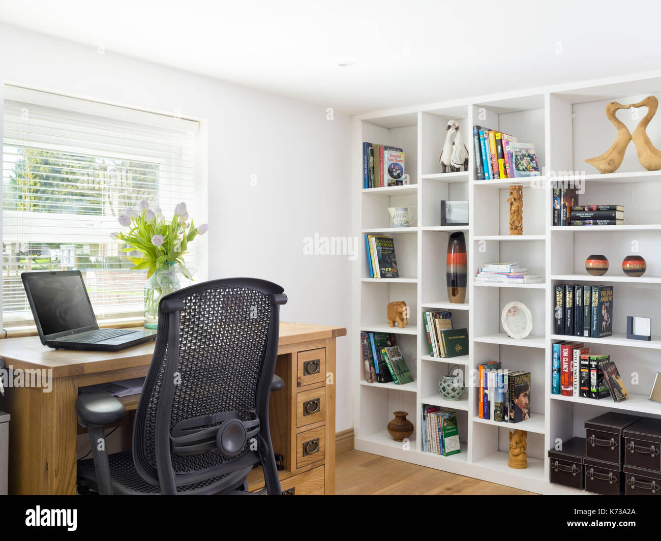 A pleasant home office in a contemporary home with oak desk, laptop and shelving - Stock Image