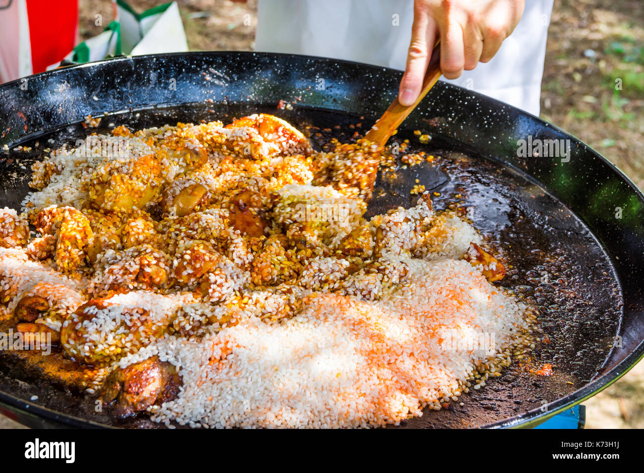 Man's hand holding wooden turner, mixing uncooked rice with fried chicken meat tomato sauce spices. Preparing paella or jambalaya. Outdoors, picnic, f - Stock Image